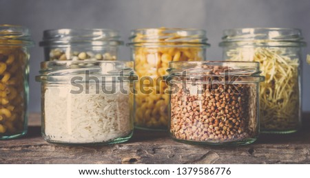Various raw cereals, grains, beans and pasta for cooking healthy food in glass jars on a wooden table, on a gray background,  Clean food, vegan, balanced diet,zero waste,eco friendly,plastic free #1379586776