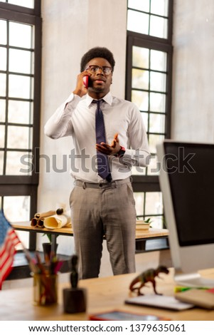 Business meeting. Handsome young man speaking on the phone while making an appointment with his client #1379635061