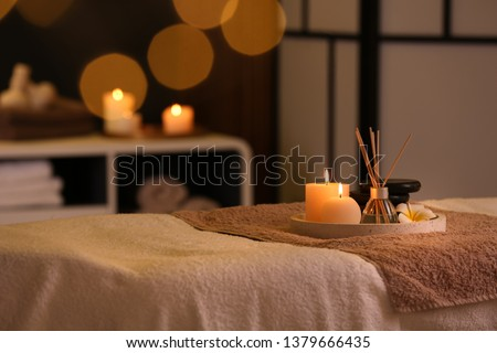 Burning candles and aromatic reed freshener on table in spa salon, space for text #1379666435