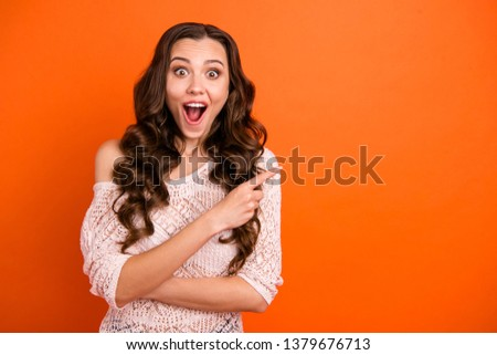 Portrait of nice attractive lovely pretty gorgeous cheerful cheery wavy-haired lady in transparent blouse pointing aside copy empty blank space isolated over bright vivid shine orange background #1379676713