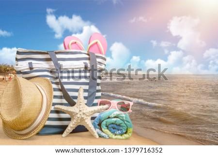 Straw hat, bag,  flip flops on a tropical beach #1379716352