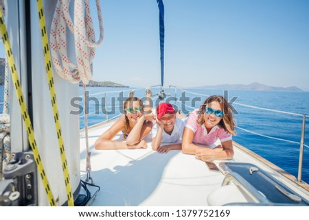 Happy family - mother with adorable daughter and son resting on a big yacht #1379752169