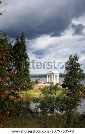 Monrepos Park (English landscape park). Vyborg. Russia. Leningrad Region. The Temple of Neptune, Antique Pavilion at the Stone Cape in Vyborg Bay with thunderclouds. Sunny summer nature photo #1379753948
