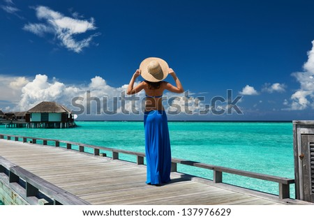 Woman on a tropical beach jetty at Maldives #137976629
