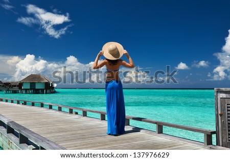 Woman on a tropical beach jetty at Maldives #137976629