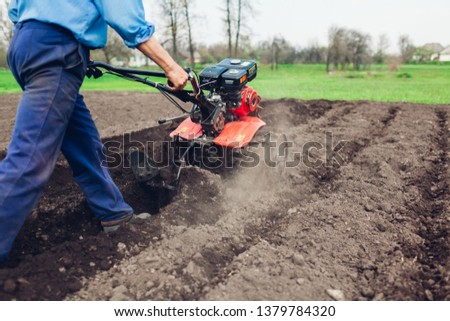 Farmer driving small tractor for soil cultivation and potato planting. Spring preparation #1379784320