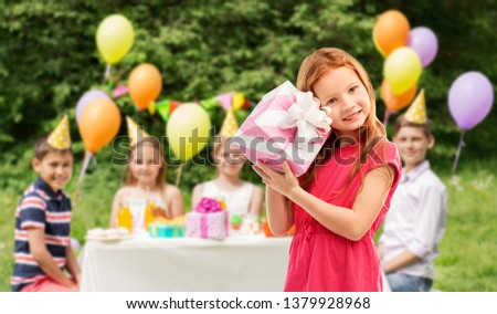 birthday and people concept - lovely red haired girl with gift box over party at summer park #1379928968