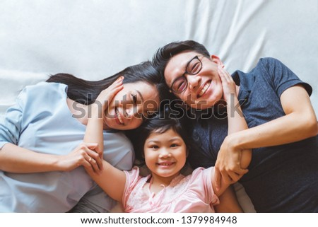 Happy Asian family laying on bed in bedroom with happy and smile, top view #1379984948