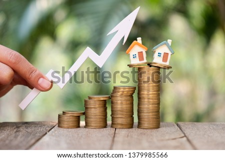Businessperson's Hand Holding Arrow Over Stacked Coins With House Models. Home model and arrow graph with growing. Business investment the real estate concept. Fund of real estate concept. #1379985566