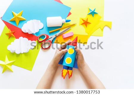 hands of the child make a paper craft rocket. Cosmos clouds and stars colored paper. The creative process. Kindergarten and school development. Master Class. Royalty-Free Stock Photo #1380017753