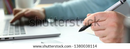 A young designer holds pen from tablet in hand working on new project for customer in field of building construction projects. #1380038114