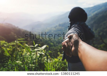 Couple summer vacation travel. Woman walking on romantic holidays holding hand of wife following her at scenic summer mountains landscape.Tourism vacation and travel. #1380111245