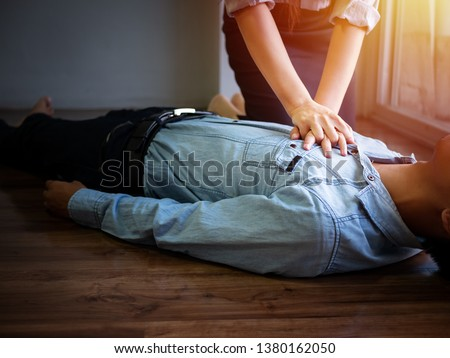 volunteer office woman use hand pump on chest for first aid emergency CPR on heart attack man unconscious, try to resuscitation patient man at work #1380162050