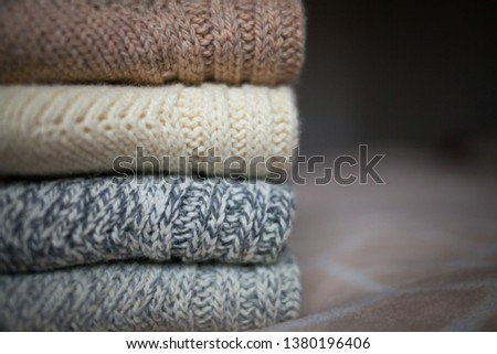 Stack of cozy knitted wool clothes on the bed. Retro style. Warm comfortable concept. Handmade job. #1380196406