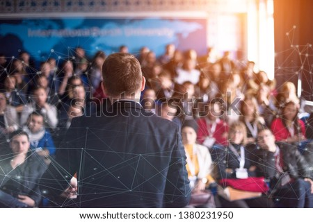 rear view of young successful businessman at business conference room with public giving presentations. Audience at the conference hall. Entrepreneurship club Royalty-Free Stock Photo #1380231950