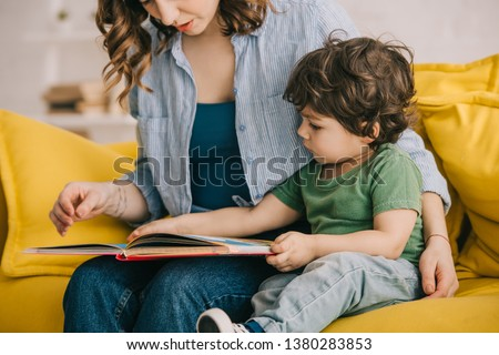 Cropped view of mother and son reading book together #1380283853