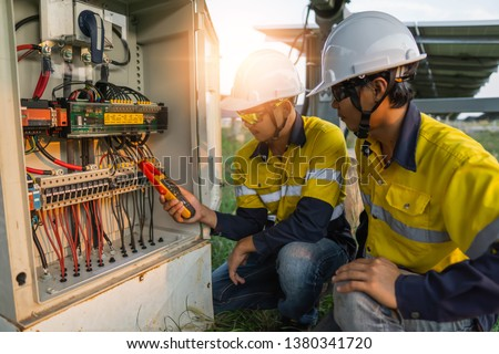 Workers use clamp meter to measure the current of electrical wires produced from solar energy for confirm to normal current. #1380341720