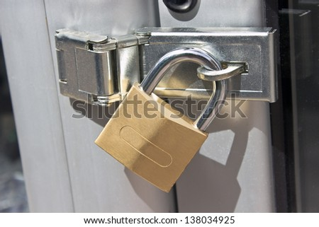 Closed padlock on  a metal door #138034925