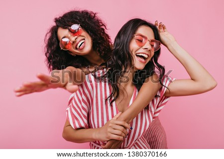 African girl hugs her sister and reaches for camera. Young women in high spirits posing over isolated background #1380370166