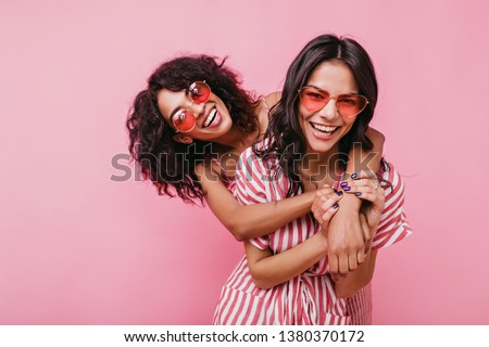 Young, spectacular models vigorously pose for portrait in studio. Tanned sisters embrace and laugh in unusual glasses #1380370172