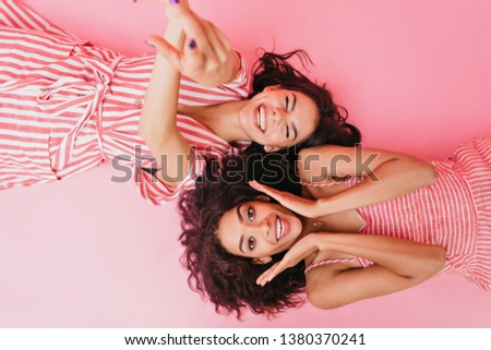 Two gorgeous dark-haired girls on pink background posing in front of camera, lying on their backs with sincere smiles on their face #1380370241