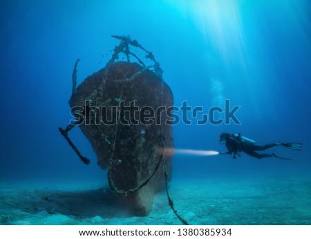 Female scuba diver with a torch explores a sunken shipwreck at the Maldives islands #1380385934