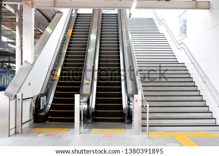 Modern luxury escalators facilities leading down into a Subway Station with Neon Lights, Moving Staircase #1380391895
