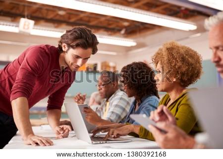 Teacher Helping Mature Woman Attending IT Class In Community Centre #1380392168