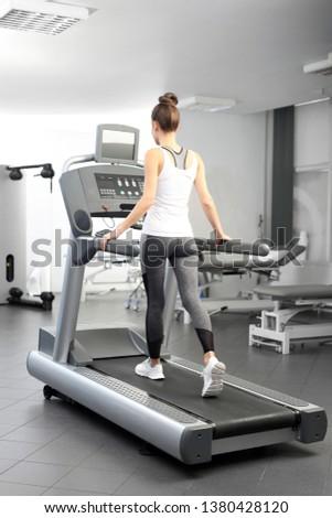 Training on the treadmill. The woman runs on an automatic treadmill #1380428120