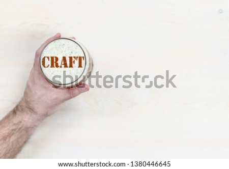 """man's hand holds a mug of beer with silhouettes of word """"craft"""". Top view. Empty space for text #1380446645"""