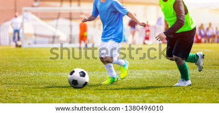 Young Boys in Blue and Yellow Soccer Jersey Shirts and Soccer Cleats Kicking Soccer Ball. Football Tournament for Youth Soccer Clubs Academies. School Sports Competition #1380496010
