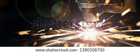 Sparks fly out machine head for metal processing laser metal on metallurgical plant background. Manufacturing finished parts for automotive production concept #1380508700