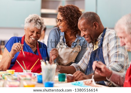 Group Of Retired Seniors Attending Art Class In Community Centre With Teacher Royalty-Free Stock Photo #1380516614