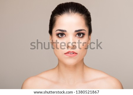 Closeup of good looking woman with blank expression against plain background #1380521867