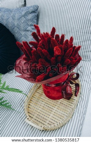 Red flowers on rustic wooden serving tray on bed at home #1380535817