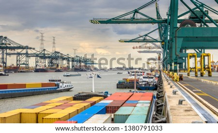 Loaded ships in busy port of Antwerp at container terminal with automated cranes and lots of vessels. Belgium Royalty-Free Stock Photo #1380791033