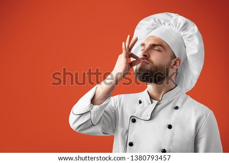 Professional chef man showing sign for delicious. Male chef in white uniform with perfect sign. Serious satisfied bearded chef, cook or baker gesturing excellent. Cook with taste approval gesture. Royalty-Free Stock Photo #1380793457