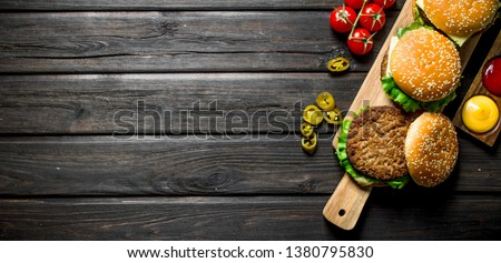 Burgers with different sauces,jalapenos and tomatoes. On black wooden background #1380795830