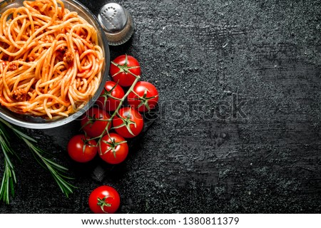 Spaghetti with Bolognese sauce in bowl with tomatoes, rosemary and spices. On black rustic background #1380811379