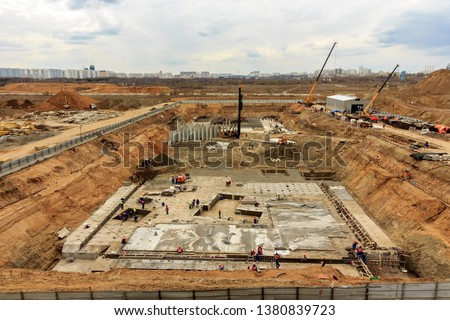 Pile driving in foundation pit for construction of apartment building. Piling driven into ground. Deep foundation installation. Reinforce prestressed concrete piles for factory foundation construction #1380839723