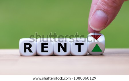Symbol for increasing rent. Hand is turning a dice and changes the direction of an arrow symbolizing that rents are going up (or vice versa). Royalty-Free Stock Photo #1380860129