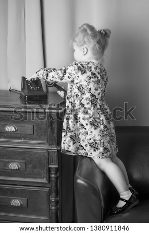 A beautiful little girl in a room in the fifties of the last century, talking on an old phone with a big black tube. Retro style, black and white photo in the studio. Concept of nostalgia, vintage.