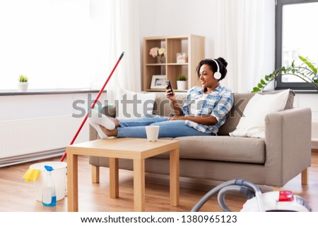 household and technology concept - happy african american woman or housewife in headphones with smartphone resting after home cleaning, listening to music and singing #1380965123