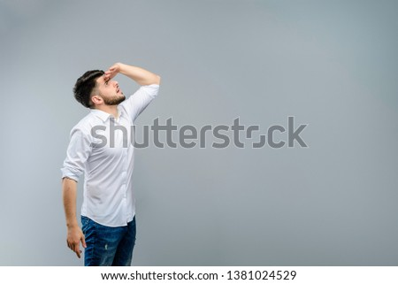 Young man looking at copyspace above his head isolated over grey background #1381024529