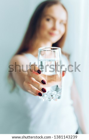 Happy beautiful young woman drinking water. Smiling caucasian female model holding transparent glass in her hand. Closeup. Focus on the arm #1381143239