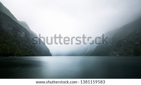 Paddeling with a kayak through the beautiful fjord landscape with high waterfalls to the famous Geiranger Fjord in Norway #1381159583