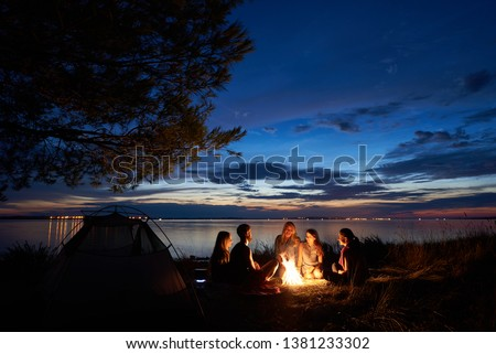 Night summer camping on lake shore. Group of five young happy tourists sitting in high grass around bonfire near tent under beautiful blue evening sky. Tourism, friendship and beauty of nature concept #1381233302