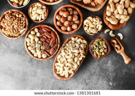 Mix of nuts in wooden bowls on dark stone table top view. Walnuts, cashew, almond, pistachio, pecan, hazelnut, macadamia nut. Healthy various super food selection. #1381301681
