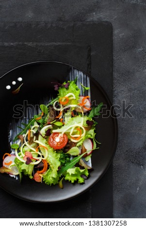 Green salad with microgreens on a black plate top view #1381307258