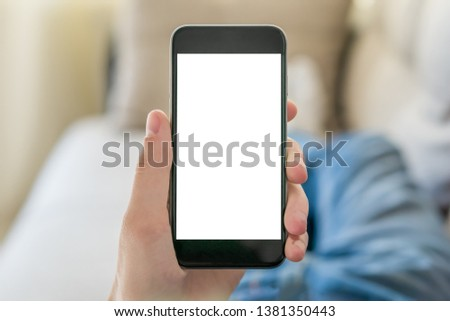 Mockup image of hand holding black mobile phone with blank white screen. Student lying on the couch and looks at the vertically positioned smartphone screen. Close up. #1381350443